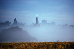A church spire pierces the early morning mist covering a village, Leicestershire, England, UK.