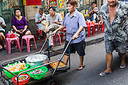 11 SEPTEMBER 2013 - BANGKOK, THAILAND:  A woman pushes a cart of fresh curry, rice and noodles to a curry stand in the Chinatown section of Bangkok. Thailand in general, and Bangkok in particular, has a vibrant tradition of street food and eating on the run. In recent years, Bangkok's street food has become something of an international landmark and is being written about in glossy travel magazines and in the pages of the New York Times.        PHOTO BY JACK KURTZ