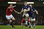 Jonny Gray of Scotland breaks away from a tackle from Gareth Davies of Wales and Aaron Shingler of Wales (l) early in the match. Wales v Scotland, NatWest 6 nations 2018 championship match at the Principality Stadium in Cardiff , South Wales on Saturday 3rd February 2018.<br /> pic by Andrew Orchard, Andrew Orchard sports photography