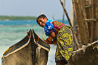 Kuna Indian woman wearing native costume with Mola embrodery with dugout canoes, Corbisky Island, San Blas Islands (Kuna Yala), Caribbean Sea, Panama