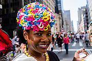 New York, NY - April 16, 2017. A woman from The Milliners Guild wears a hat decorated in brightly colored pipe cleaners at New York's annual Easter Bonnet Parade and Festival on Fifth Avenue.
