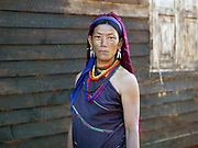 Portrait of a Kayah Red Karen ethnic minority woman in village of Kle Du, Kayah State, Myanmar on 20th November 2016.  Myanmar is one of the most ethnically diverse countries in Southeast Asia with 135 different indigenous ethnic groups with over a dozen ethnic Karenni subgroups in the Kayah region. Kayah women wear a simple striped tunic worn with a broad white sash decorated with coloured tassles and a striped hand-woven head-cloth