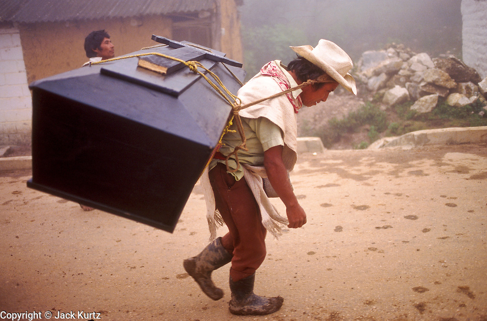 SAN ANDRES LARRAINZAR, CHIAPAS, MEXICO: A Chamulan Indian man with his uncle's coffin walks along a mountain road near town of San Andres Larrainzar, Chiapas, Mexico.  ©  JACK KURTZ   FAMILY  POVERTY  INDIGENOUS   CULTURE  LAND ISSUES
