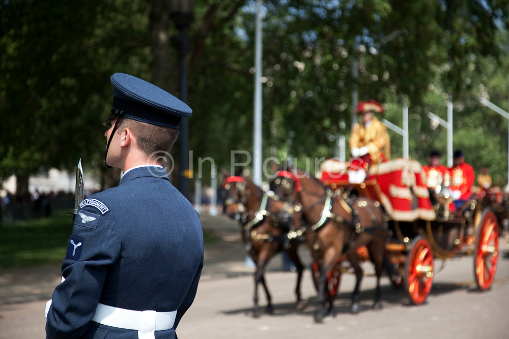 Horse drawn coach approaches as a member of the RAF Regiment stands guard. Royal procession for the State Opening of Parliament, London. This procession takes Queen Elizabeth to parliament to deliver the Queen's Speech.