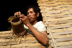 Mr Luang is deaf mute 29 years old, lives with his sister Pan and makes baskets from bamboo that he sells in the village. Naluang Village, Nambac District, Luang Prabang Province. Lao PDR