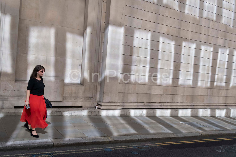 In the week that many more Londoners returned to their office workplaces after the Covid pandemic, a woman City worker walks past sun reflections on the walls of the Bank of England in the City of London, the capitals financial district, on 8th September 2021, in London, England.