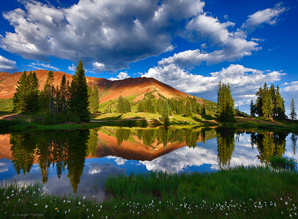 Cumulus clouds build in late afternoon. This high alpine lake always provides spectacular mountain reflections.