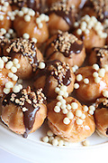cream puffs dessert decorated with chocolate sauce and sweets