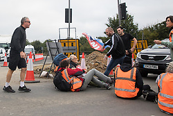 Enfield, UK. 15th September, 2021. Angry motorists remove banners from Insulate Britain climate activists blocking a slip road from the M25 at Junction 25 as part of a campaign intended to push the UK government to make significant legislative change to start lowering emissions. The activists, who wrote to Prime Minister Boris Johnson on 13th August, are demanding that the government immediately promises both to fully fund and ensure the insulation of all social housing in Britain by 2025 and to produce within four months a legally binding national plan to fully fund and ensure the full low-energy and low-carbon whole-house retrofit, with no externalised costs, of all homes in Britain by 2030 as part of a just transition to full decarbonisation of all parts of society and the economy.