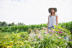 Mid adult woman standing with flowers in her community garden, Bavaria, Germany