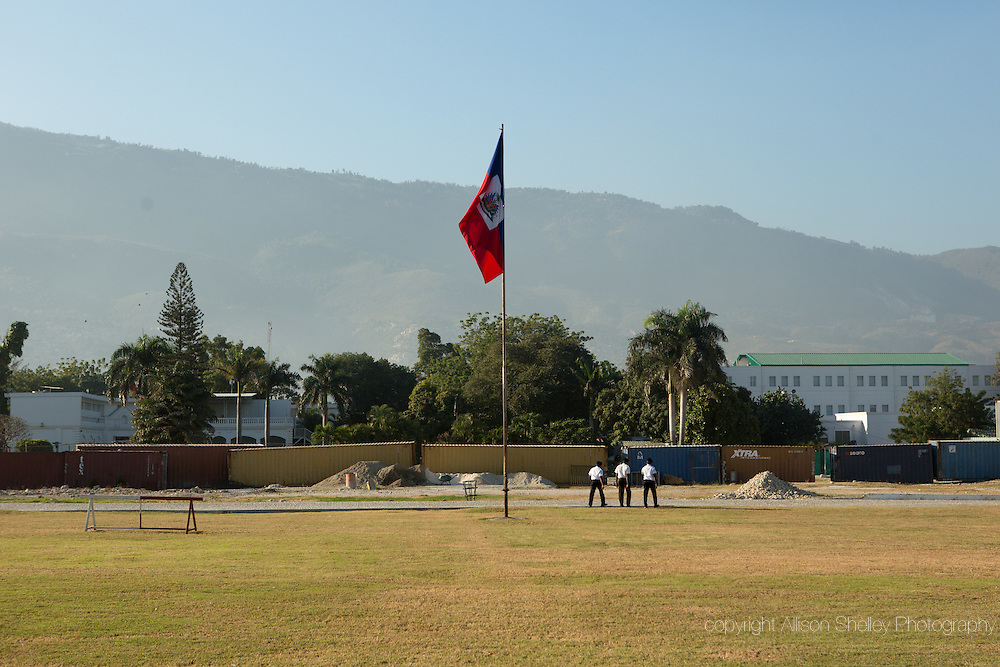 Officials march away after raising the Haitian flag on the national palace grounds in downtown Port-au-Prince, Haiti, the morning of January 10, 2015.  This ritual happens every morning despite the fact that the grounds are now shielded from public view by a large green fence.  The demolition and clearance of the destroyed palace was done by the American NGO J/P HRO in 2012.