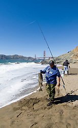 California, San Francisco:  Fisherman with striped bass at Baker Beach near the Golden Gate Bridge.Photo #: 2-casanf83727.Photo © Lee Foster 2008