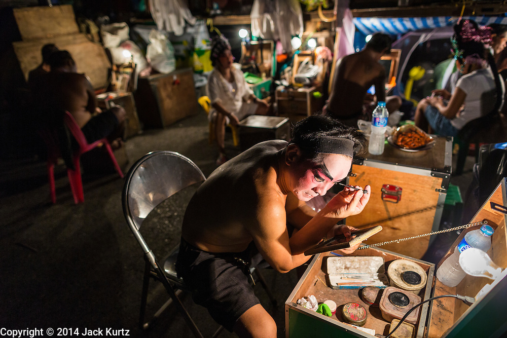 """19 AUGUST 2014 - BANGKOK, THAILAND:  A member of the Lehigh Leng Kaitoung Opera troupe applies his makeup before a performance at Chaomae Thapthim Shrine, a small Chinese shrine in a working class neighborhood of Bangkok. The performance was for Ghost Month. Chinese opera was once very popular in Thailand, where it is called """"Ngiew."""" It is usually performed in the Teochew language. Millions of Chinese emigrated to Thailand (then Siam) in the 18th and 19th centuries and brought their culture with them. Recently the popularity of ngiew has faded as people turn to performances of opera on DVD or movies. There are still as many 30 Chinese opera troupes left in Bangkok and its environs. They are especially busy during Chinese New Year and Chinese holiday when they travel from Chinese temple to Chinese temple performing on stages they put up in streets near the temple, sometimes sleeping on hammocks they sling under their stage. Most of the Chinese operas from Bangkok travel to Malaysia for Ghost Month, leaving just a few to perform in Bangkok.           PHOTO BY JACK KURTZ"""