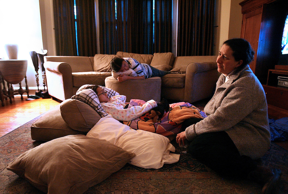 """2/14/2009 Baltimore, MD-  Lani Dickinson, 14, is comforted by her mother Julie Bell in a friend's house in the Baltimore area a day after Lani's surgery for the """"revision of her transhumeral amputation.""""  Lani was born in China with a congenital defect and adopted by an American family.  Despite her disability, she trains hard as a ballerina and would like to someday be a professional dancer.  Photo by Lisa Hornak"""