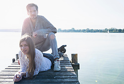 Sunset young couple relaxing lake jetty