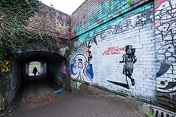 "© Licensed to London News Pictures; 14/03/2021; Bristol, UK. People are seen at the end of a tunnel past a mural in the style of Banksy with an image of a girl and with the words ""There is light at the end of the tunnel"", by the railway off Muller Road in Bristol. According to some locals it has been painted very recently, perhaps early this morning. Banksy often comments on current events, and if the piece is by Banksy it could be a reference to the end of the covid-19 coronavirus pandemic, or to social movements such as #MeToo, Black Lives Matter, or Reclaim the Streets. Photo credit: Simon Chapman/LNP."