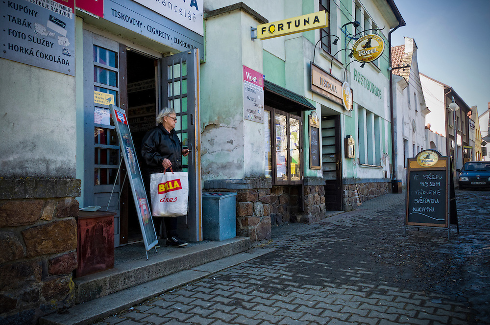 DIVISOV, CZECH REPUBLIC - MARCH 4th 2010: Resident of  Divisov in the Czech Republic, going out of small commerce in the village, this is a very small town in the Moravia Region.