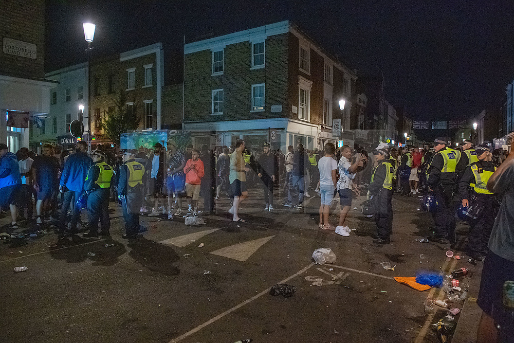 © Licensed to London News Pictures. 19/07/2020. London, UK. The crowd gathered at the corner of Kensington Park Road and Blenheim Cresent. A crowd has been dispersed by police from Kingsington Park Road in Notting Hill. The crowd was ordered to leave the area under a Section 35 order. The Crowd were generally compliant and left the area peacefully. Photo credit: Peter Manning/LNP