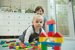 Mother and her little son with building bricks
