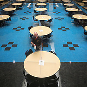 Dan Sprague, custodian, sprays dividers on tables with disinfectant between lunches at Perrysburg High School in Perrysburg, Ohio, on Thursday, Sept. 3, 2020. THE BLADE/KURT STEISS