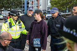 London, UK. 4 September, 2019. Metropolitan Police officers arrest an anti-nuclear activist who had locked herself to another activist to attempt to block one of the two main access roads to ExCel London during protests on the third day of a week-long carnival of resistance against DSEI, the world's largest arms fair. The third day's protests were organised by the Campaign for Nuclear Disarmament (CND) and Trident Ploughshares.