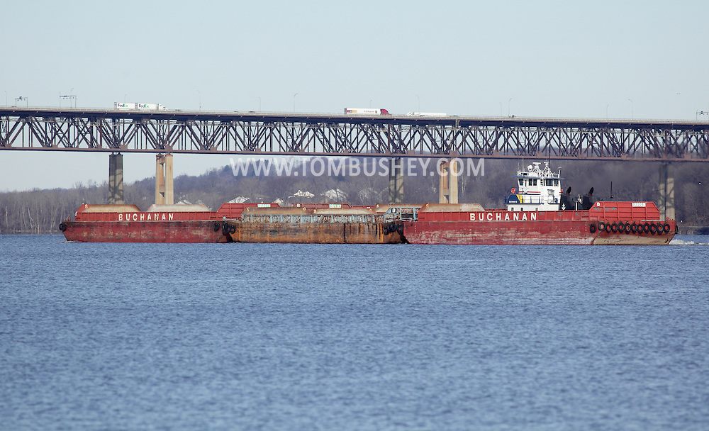 Newburgh, New York - The tugboat Buchanan 12 pushes barges up the Hudson River on Dec. 29, 2011. Trucks and cars travel across the Newburgh-Beacon Bridge in the background.