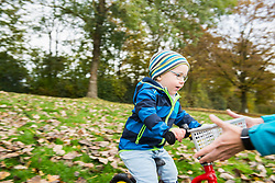 Little boy driving with his walking bicycle towards arms of mother in autumn scenery