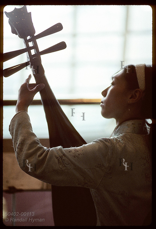 Silhouette of young woman playing Chinese lute, or pi-pa, shows the four lateral tuning pegs. China
