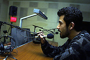"""Wahid Ahmadi a technician at """"Good Morning Afghanistan"""" tests a microphone in the studio the day beofre the programme goes on air at Kabul radio."""