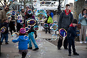 A walk along the River Thames on the Southbank in London. Children play with bubbles. This area is very popular especially on the weekends for Londoners to walk and see different arts, culture and entertainment.