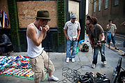 Harmonica player and guitaristat Brick Lane Market. Many people come to sell their cast-off clothes and belongings to raise some cash. Official stalls selling clothers, food and all manner of crafts and junk make up the mainstay of the market though. These unofficial sellers though give the market it's unique atmosphere. This market is a weekly event in London's East End.