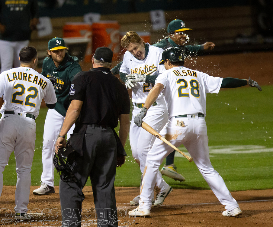 Sep 25, 2020; Oakland, California, USA; Oakland Athletics Mark Canha (20) is greeted by his teammates after hitting a game-winning two-run home run against the Seattle Mariners during the tenth inning of a Major League Baseball game at Oakland Coliseum. Mandatory Credit: D. Ross Cameron-USA TODAY Sports