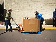"""11 MAY 2020 - DES MOINES, IOWA: RICHARD JESS and GRACE OSTRANDER move a pallet of food packages at a """"no touch"""" emergency food pantry at DSM First Church in Des Moines. The emergency pantry at DSM First Church expanded from distribution one day a week to three days per week after the COVID-19 pandemic forced the closure of many Iowa businesses. Food banks and emergency pantries in Iowa continue to see increased demand for services, even though the governor is reopening the state's economy. Iowa's unemployment rate for April hasn't been released yet, but based on national trends, it is expected to soar to well over 10% from 3.8& in March. COVID-19 infections continue to skyrocket. On Monday, 11 May, the governor announced that 12,373 people tested positive for coronavirus (SAR-CoV-2) and  271 had died.             PHOTO BY JACK KURTZ"""