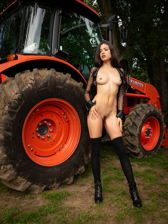 Nude woman wearing a black sheer top and black stockings standing in front of a red tractor