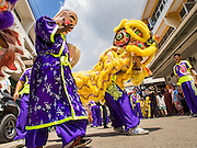 """05 JULY 2014 - BANGKOK, THAILAND: Chinese style lion dancers perform on a side street in Bangkok during a parade for vassa. Vassa, called """"phansa"""" in Thai, marks the beginning of the three months long Buddhist rains retreat when monks and novices stay in the temple for periods of intense meditation. Vassa officially starts July 11 but temples across Bangkok are holding events to mark the holiday all week.    PHOTO BY JACK KURTZ"""