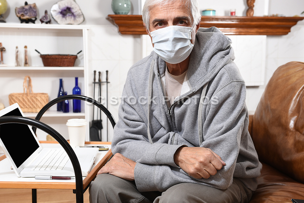 Man Not Feeling Well Wearing a Surgical Face Mask at Home