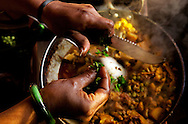 One of the women cooking at Astitva chops herbs and drops them into a pan of cooking curried vegetables. The food is served to the day-school children, staff and to customers who buy traditional Indian tiffins for lunch. Astitva, a non-governmental organization (NG)) in Debradun, India, helps battered women become more economically independent, such as starting small businesses. It also provides the women with family services so they have time to pursue their business interests. Dehradun is a city of 575,000 about six hours north of New Delhi by train. Nestled next to the Himalayan foothills, it's a little off the path for most tourists. Astitva is located in a neighborhood where poor and upper class people live within close proximity.