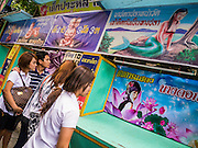 """27 NOVEMBER 2012 - BANGKOK, THAILAND:  Thai teenagers walk past the freak show tent at the Wat Saket Temple Fair in Bangkok. Wat Saket, popularly known as the Golden Mount or """"Phu Khao Thong,"""" is one of the most popular and oldest Buddhist temples in Bangkok. It dates to the Ayutthaya period (roughly 1350-1767 AD) and was renovated extensively when the Siamese fled Ayutthaya and established their new capitol in Bangkok. The temple holds an annual fair in November, the week of the full moon. It's one of the most popular temple fairs in Bangkok. The fair draws people from across Bangkok and spills out in the streets around the temple.   PHOTO BY JACK KURTZ"""