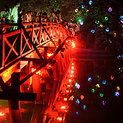 The Huc Bridge (Morning Sunlight Bridge) colorful lights. The red-painted, wooden bridge joins the northern shore of the lake with Jade Island and the Temple of the Jade Mountain (Ngoc Son Temple).