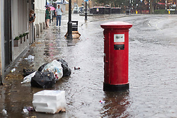 © Licensed to London News Pictures. 25/07/2021. London, UK. A women films a section of flooded road in Greenwich Town Centre in South East London . An amber weather warning for thunderstorms is in place in parts of London and the South East . Photo credit: George Cracknell Wright/LNP