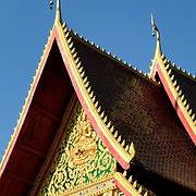 The ornately and colorfully decorated roof of a Wat (Buddhist Temple) in Vientiane, Laos.