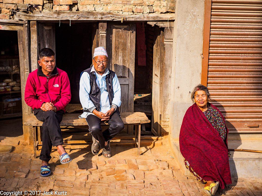 15 MARCH 2017 - BUNGAMATI, NEPAL: People in front of a small shop damaged in the 2015 Nepal earthquake in Bungamati. Bungamati, a community of wood carvers and artisans, used to be a stop on the tourist trail of the Kathmandu valley but since the 2015 earthquake few tourists visit the community. Recovery seems to have barely begun nearly two years after the earthquake of 25 April 2015 that devastated Nepal. In some villages in the Kathmandu valley workers are working by hand to remove ruble and dig out destroyed buildings. About 9,000 people were killed and another 22,000 injured by the earthquake. The epicenter of the earthquake was east of the Gorka district.            PHOTO BY JACK KURTZ