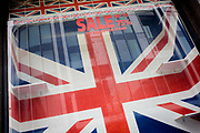 British Union jack flags-themed tourist window, now closed with displays removed after recent sale. A diagonal angle on the large flag that is spread across the window with the reflection of a nearby building. The business was on Oxford Street in London's West End and specialised in tourism trinkets before closing, its window display removed except for the flags and lettering telling us the last Sale gave up to 75% discounts on selected items. The scene left by the owners is that of a sad end to another business forced to close by economic hardship. Even the space on empty shelves seems tragic.