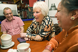 Group of friends sitting around a table in a café chatting,,
