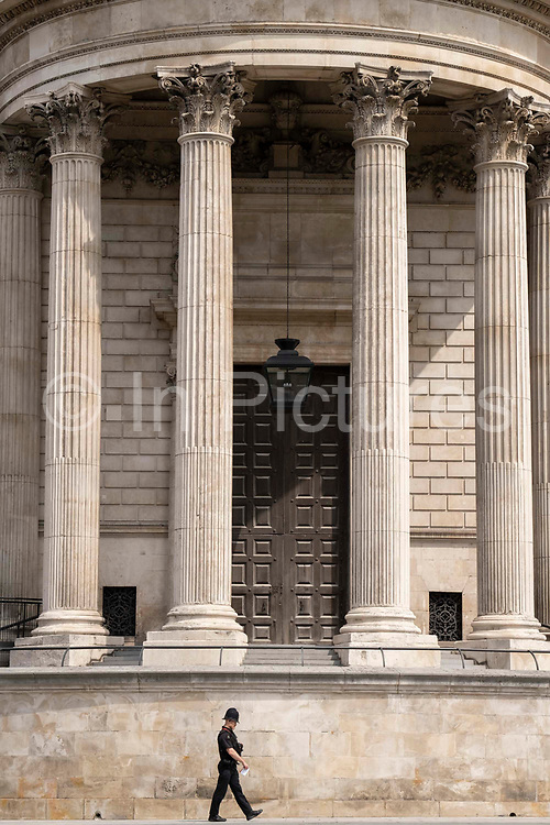 A City of London police officer patrols the street beneath the pillars and column architecture of Sir Christopher Wrens St Pauls Cathedral south transept, on 24th June 2021, in London, England.