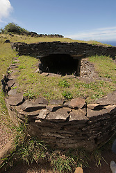 Chile, Easter Island: Orongo Village, restored archeological site where the birdman cult was practiced.  The birdman cult decided king-of-year governance by requiring athletes to bring the first egg of the season from offshore islands.  The athlete's patron became king.  The site has stone houses, petroglyphs, and a crater lake where the athletes cut reeds to make rafts to get to the island..Photo #: ch270-33720..Photo copyright Lee Foster www.fostertravel.com lee@fostertravel.com 510-549-2202