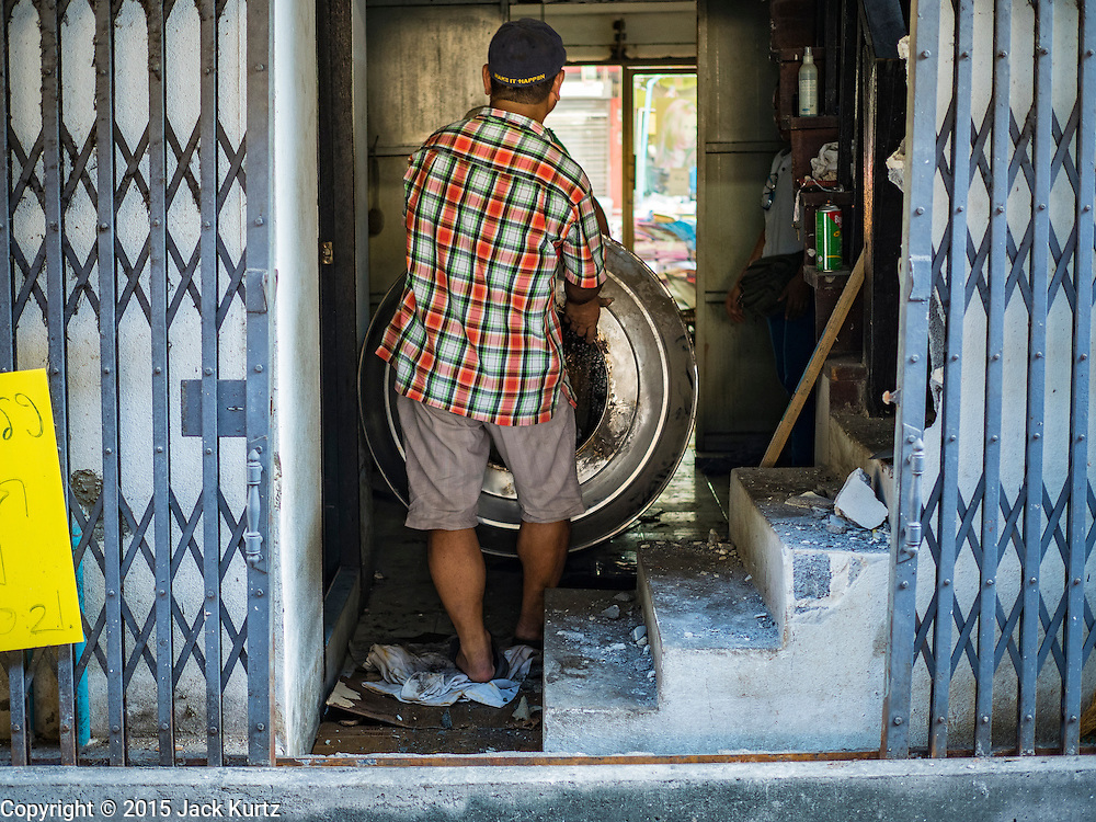 31 DECEMBER 2015 - BANGKOK, THAILAND: A demolition worker pulls a water tank out of a beauty shop he is tearing down in Bang Chak Market after the shop was closed. The market is supposed to close permanently on Dec 31, 2015. The Bang Chak Market serves the community around Sois 91-97 on Sukhumvit Road in the Bangkok suburbs. About half of the market has been torn down. Bangkok city authorities put up notices in late November that the market would be closed by January 1, 2016 and redevelopment would start shortly after that. Market vendors said condominiums are being built on the land.          PHOTO BY JACK KURTZ