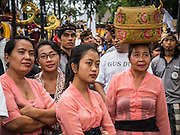 16 JULY 2016 - UBUD, BALI, INDONESIA: Women watch a sarcophagus burn during the mass cremation in Ubud. Local people in Ubud exhumed the remains of family members and burned their remains in a mass cremation ceremony Wednesday. Almost 100 people were cremated and laid to rest in the largest mass cremation in Bali in years this week. Most of the people on Bali are Hindus. Traditional cremations in Bali are very expensive, so communities usually hold one mass cremation approximately every five years. The cremation in Ubud concluded Saturday, with a large community ceremony.     PHOTO BY JACK KURTZ