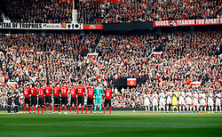 Manchester United players and Liverpool players take part in a minutes applause in memory of former Manchester United youth coach Eric Harrison during the Premier League match at Old Trafford, Manchester.