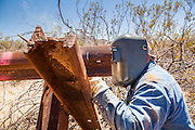 "03 MAY 2012 - VEKOL VALLEY, RURAL PINAL COUNTY, AZ:  Eric Reynolds (CQ), a BLM welder from the Safford office, works on vehicle barriers on Bureau of Land Management land south of Interstate 8 and west of Casa Grande in rural Pinal County. The area has been a hotbed of illegal immigrant and drug smuggling for years. The BLM has undertaken a series of ""surges"" in the area, increasing their law enforcement patrols and partnering with Border Patrol and Pinal County Sheriff's Department officers to reduce criminal activity in the area.        PHOTO BY JACK KURTZ"